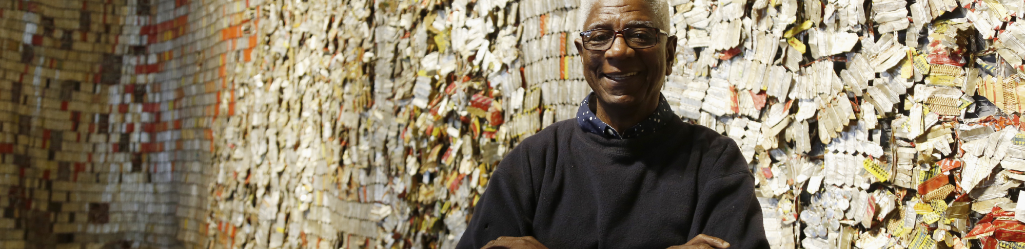 "For the past 30 years, El Anatsui has been known within Africa as one of the continent's most influential sculptors and today he is now also recognized as one of the foremost contemporary artists of his generation.Description of his work Up to 20 assistants help Anatsui flatten aluminum seals taken from thousands of liquor bottles. They then fold them into strips that are woven together with copper wire, resulting in draping cloth-like pieces that often reach sizes of 30 feet or more. Anatsui's sculptures not only transform common materials and impart new meaning to them, they also continuously evolve undergoing transformations themselves each time they are shown. About El Anatsui El Anatsui was born in 1944 in Anyako, Ghana. He earned a Bachelor's Degree in Sculpture and a Postgraduate Diploma in Art Education from the University of Science and Technology, Kumasi, Ghana. Much of Anatsui's early work made use of scorching wood with fire. Before venturing into his current ""cloth series"" he worked with the concept of fragility through ceramics and created sculptures with a chainsaw and wood. Exhibitions Many major institutions throughout the world have exhibited Anatsui's work. He received an honorable mention at the 44th Venice Biennale. In 2007 El Anatsui exhibited at the 52nd Venice Biennale with a site-specific installation, transforming one of Venice's most celebrated Gothic landmarks by wrapping the façade of the Palazzo Fortuny in a vast metal cloth. El Anatsui collectors Works by Anatsui can be seen in the permanent collections of The Metropolitan Museum of Art, NY; The Museum of Modern Art, NY; National Museum of African Art, Smithsonian Institution, Washington DC; The British Museum, London and the Pompidou Center, Paris, France, as well as many other institutions. Anatsui lives and works in Nigeria where he is a Professor of Sculpture at the University of Nigeria, Nsukka. October Gallery, London and David Krut Fine Art, New York represents El Anatsui. This is an extract from Art Interview's talk with El Anatsui:"